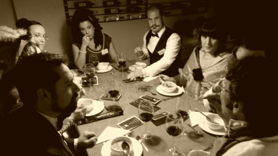El Caso de la Mansión Watersdown, jugadores escuchando a uno de los personajes en una cena con asesinato de Cluedo Sevilla